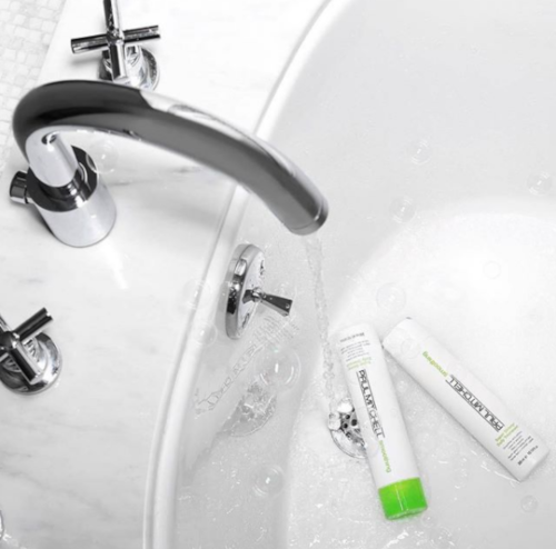Paul Mitchell Super Skinny Shampoo and Conditioner in bathtub with running water