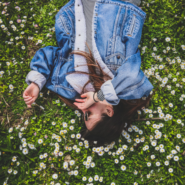 Girl in denim laying on grass with daisies